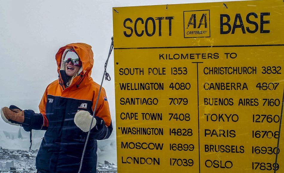 Journalistin Ashlan Gorse Cousteau posiert beim Scott Base Schild in der Antarktis. Das gelbe Schild, im Stil der neuseeländischen Automobile Association, zeigt Entfernungen von Scott Base zu verschiedenen Städten der Welt an. Von hier sind es noch 1353 km bis zum Südpol.