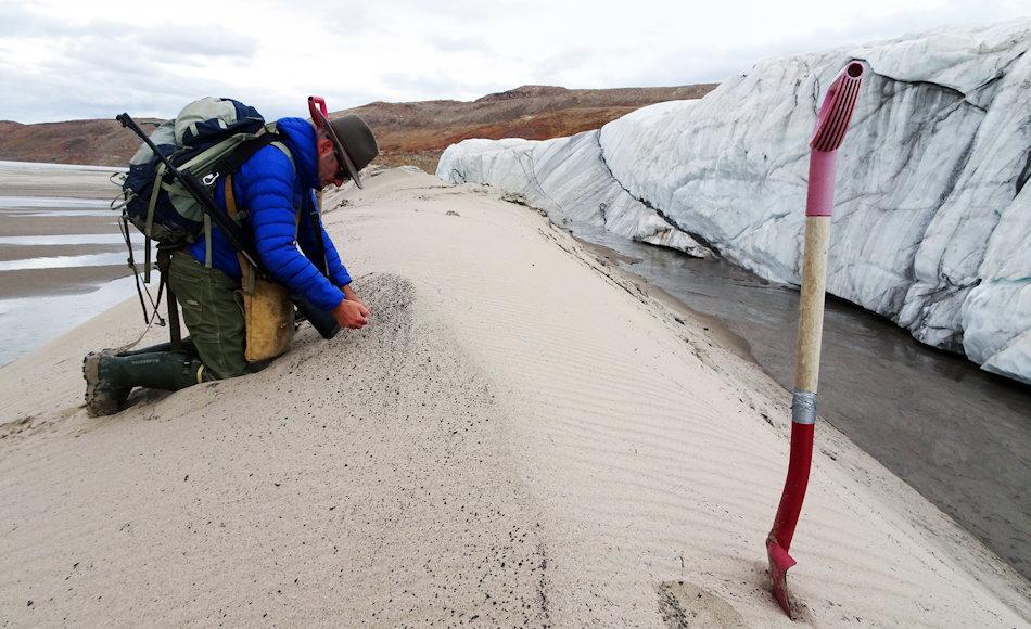 Kurt Kjær nimmt Sandproben and er Front des Hiawatha Gletschers. Der Gletscherfluss transportierte diesen Sand vom Grund des Einschlagkraters zur Eiskante. Bild: Svend Funder